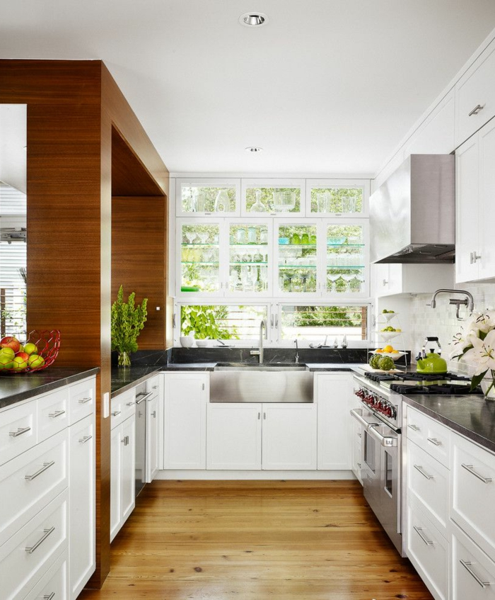 white cabinets with black granite countertops, laminated flooring, mid century modern kitchen