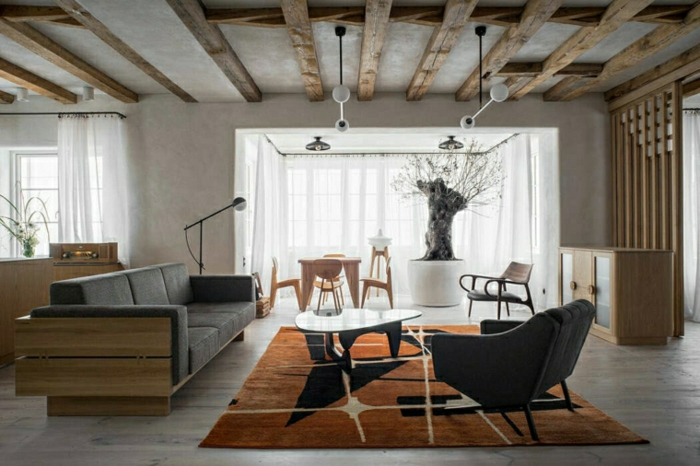 black sofa, wooden floor with orange carpet, how to decorate a living room, open plan space with living room and kitchen