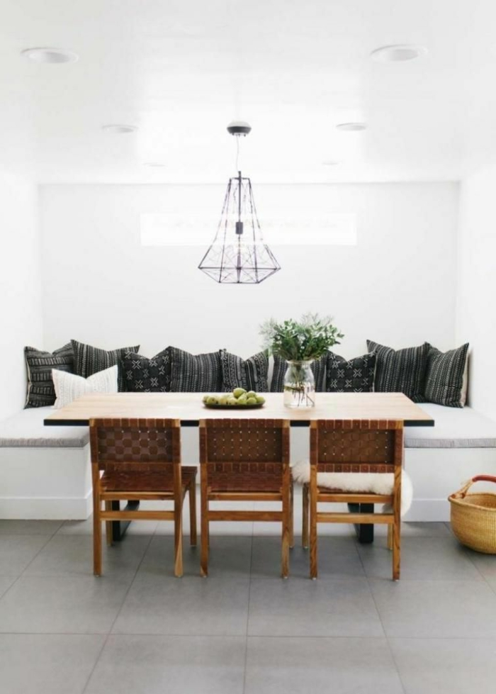 breakfast nook, black throw pillows, mid century kitchen, white table with wooden chairs, tiled floor