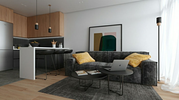 black sofa with yellow throw pillows, contemporary living room, open plan space with kitchen and living room