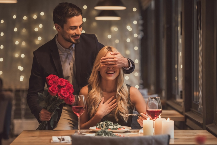 blonde woman sitting at a dinner table, wedding anniversary gifts, man covering her eyes, holding a bouquet of roses