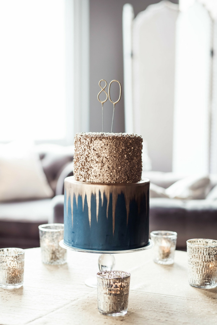 80th birthday ideas for dad, two tier cake, covered with blue and gold fondant, placed in the middle of table