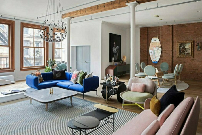 blue corner sofa with colorful throw pillows, modern living room, wooden floor and brick wall, wooden coffee table