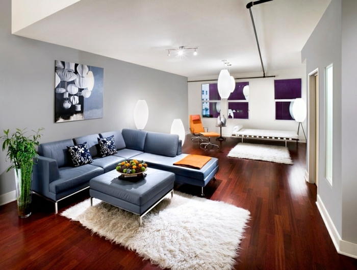 dark wooden floor, how to decorate your living room, blue leather corner sofa, blue leather ottoman, white rug