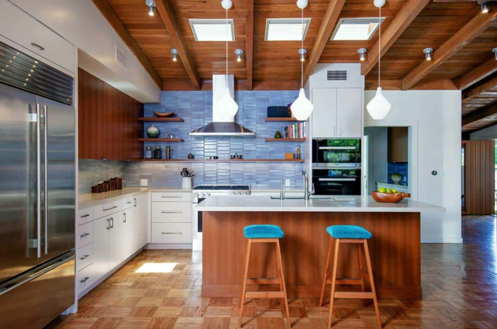 wooden kitchen island with white countertop, white cabinets, mid century modern cabinet, blue tiles backsplash