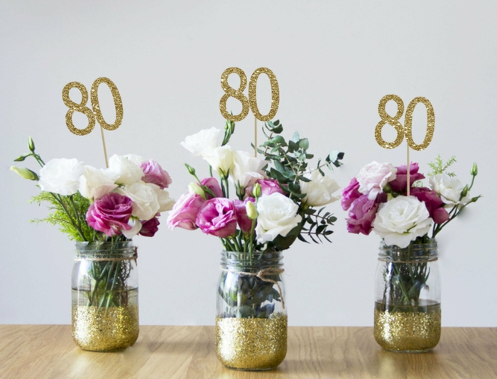 flower arrangements with white and purple roses, inside mason jars with gold glitter, 80th birthday decorations, gold glitter number 80