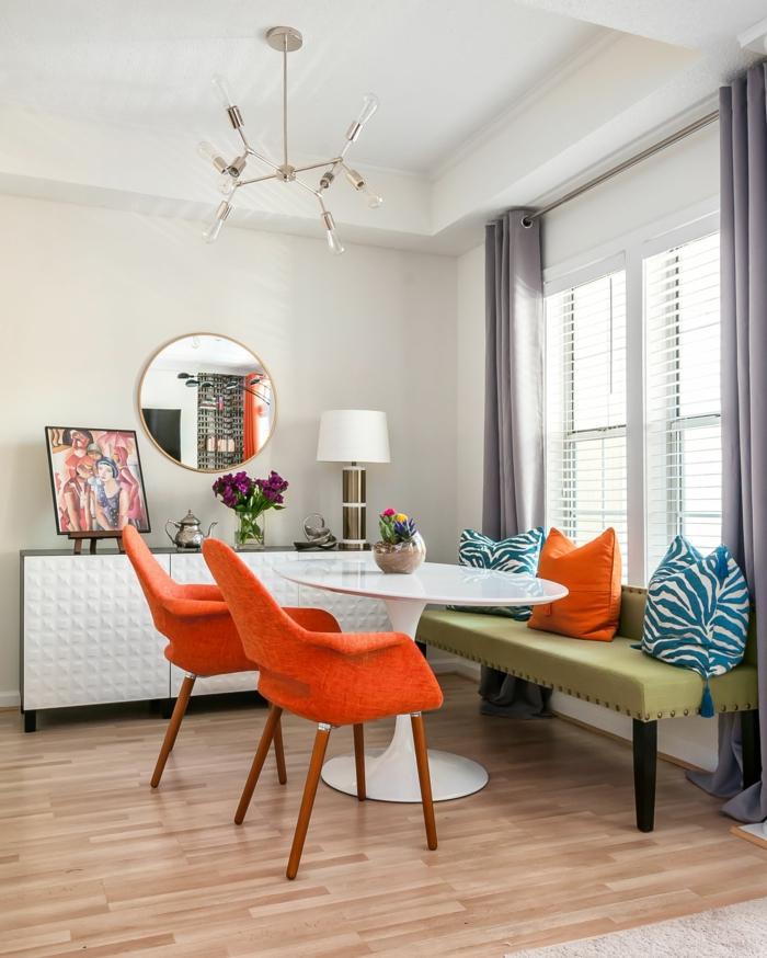 orange chairs, blue and orange throw pillows, modern kitchen cabinets, breakfast nook