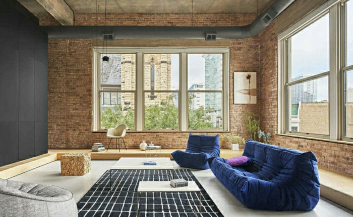 blue sofa and armchair, brick walls, decorations ideas for living room, white floor with black carpet