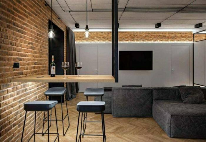brick walls in industrial apartment, large grey corner sofa, wooden bar with black bar stools, modern living room