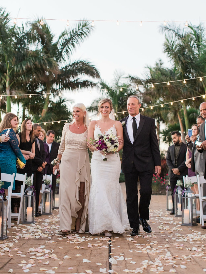 bride being walked down the aisle by her mother and father, palm trees in the background, songs to walk down the aisle to
