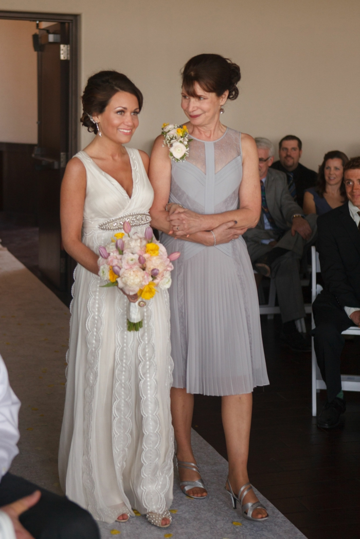 wedding entrance songs, bride being walked down the aisle by her mother, wearing a grey dress