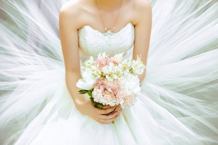 bride wearing a wedding dress, holding a bouquet, songs to walk down the aisle to, sittin down