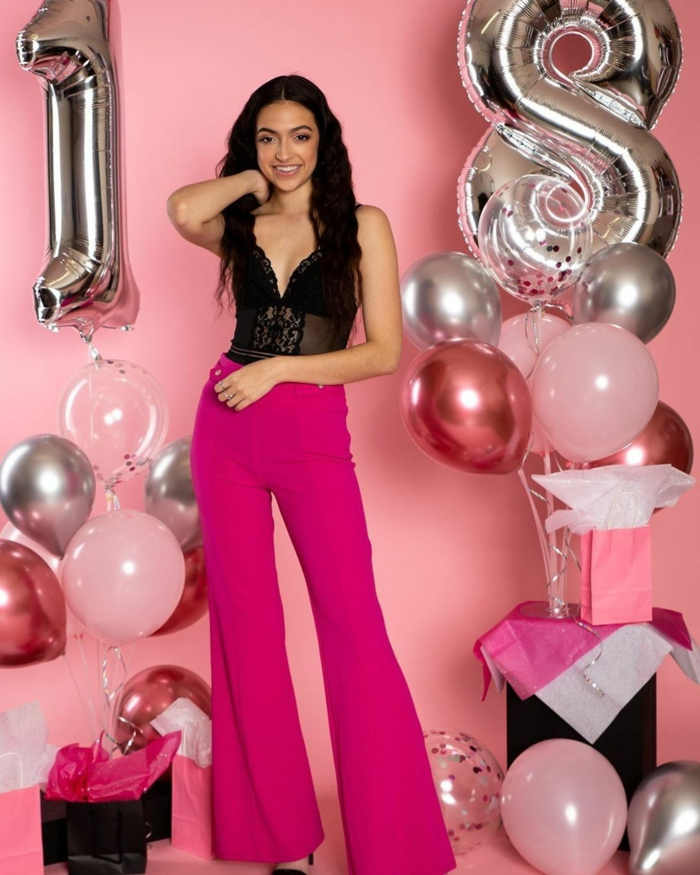 18th birthday ideas, brunette woman wearing black lace top and pink trousers, surrounded by balloons