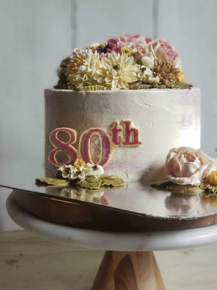one tier cake covered with white buttercream, decorated with flowers, happy 80th birthday, wooden cake stand