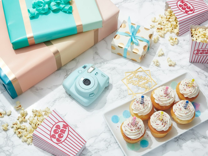 polaroid camera and popcorn, cupcakes and gifts, arranged on marble surface, birthday party themes