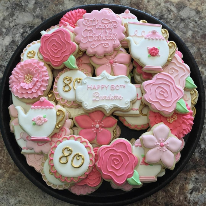 different cookies in the shapes of flowers and teapots, 80th birthday ideas for dad, arranged on black tray