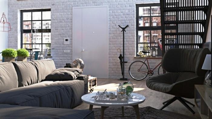 white brick wall, grey corner sofa, black armchair, modern living room decor ideas, small round coffee table