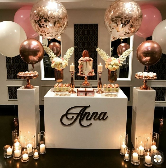 desserts table with white roses, surrounded by pink and rose gold balloons, candles on the floor, 18th birthday gifts
