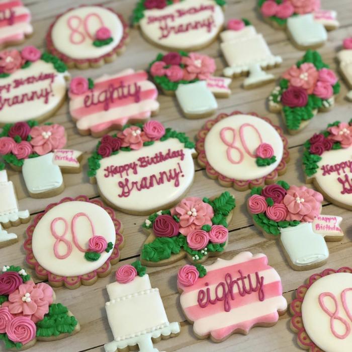 cookies in the shape of flowers and cakes, 80th birthday ideas, decorated in white purple and pink