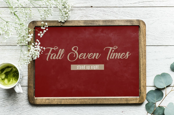 fall seven times stand up eight, written on red wooden board, tough times quotes, placed on white wooden surface