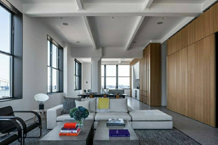 wooden accent wall, modern living room ideas, white sofa, black armchairs, grey tiled floor with grey carpet