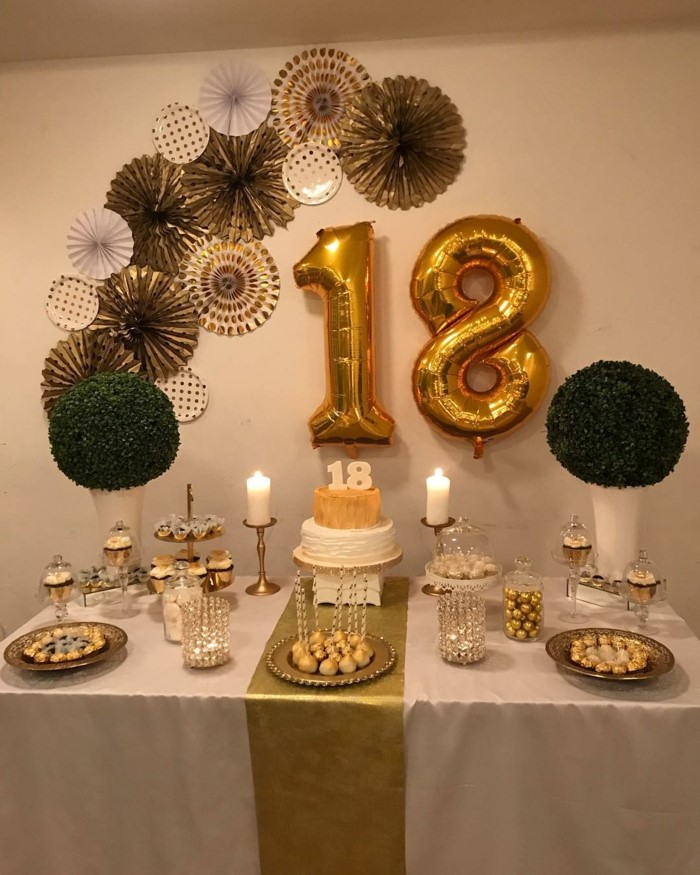 gold number 18 balloons, paper flowers on white wall, 18th birthday ideas for girls, desserts table with gold table runner