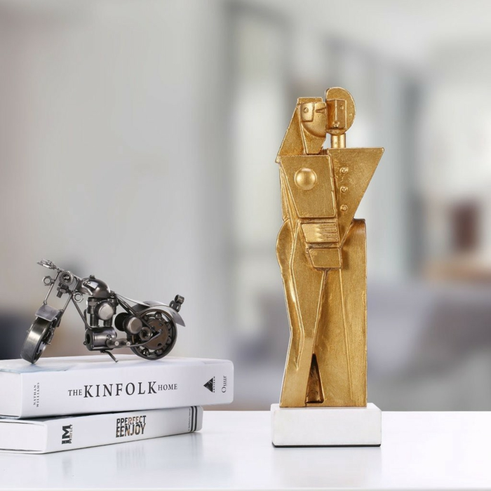 gold sculpture of man and woman hugging, traditional wedding anniversary gifts, placed on white surface, next to two books