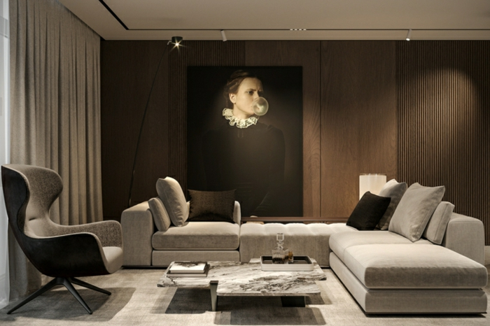 white corner sofa, grey armchair, modern living room furniture, wooden accent wall with artwork on it