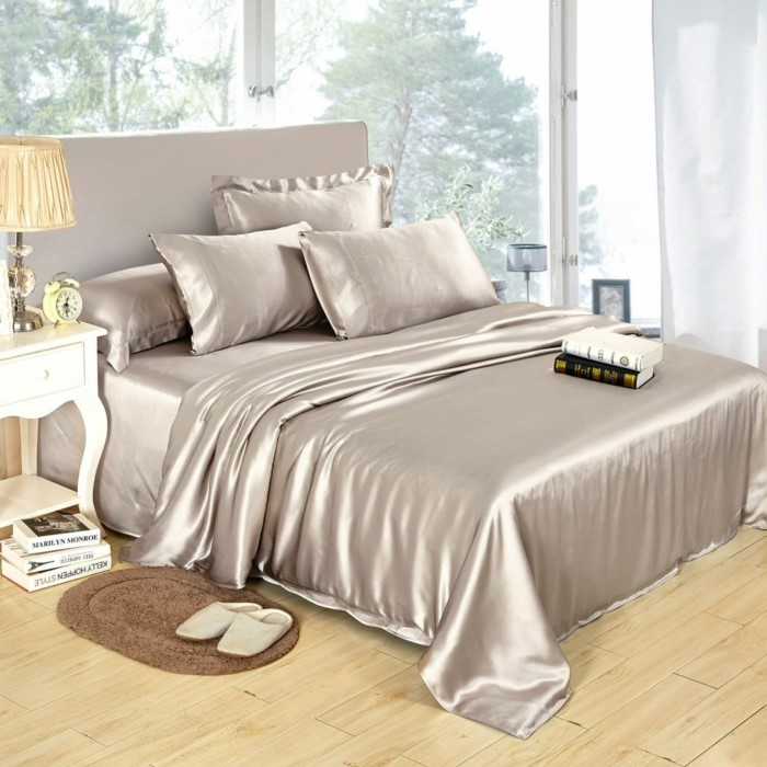 grey silk bed sheets, spread on large bed, anniversary gifts for her, white bed side table, books on the bed