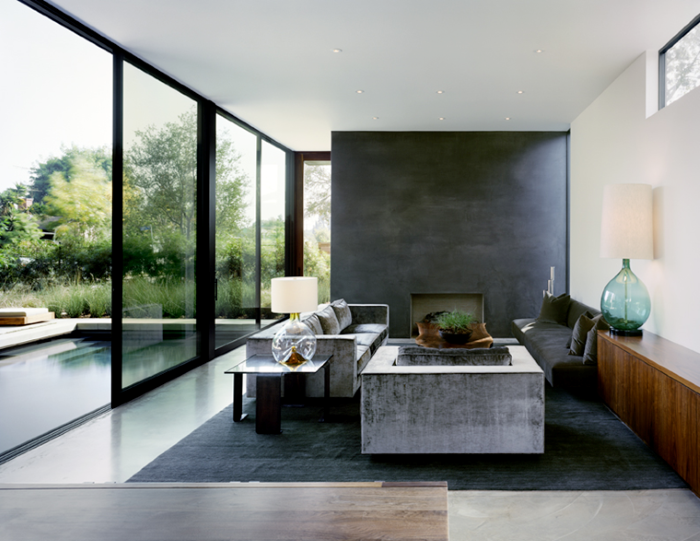 granite accent wall, luxury living room furniture, grey sofas, tall windows, grey sofa with black carpet