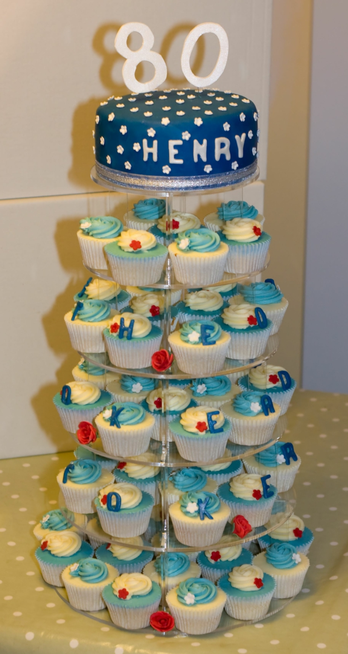 cake stand with lots of cupcakes arranged on it, one tier cake on top, 80th birthday ideas, blue fondant