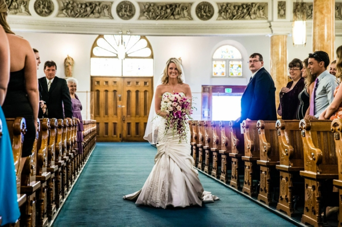 bride walking down the aisle alone, holding a large bouquet, wedding ceremony songs, photo from inside the chapel