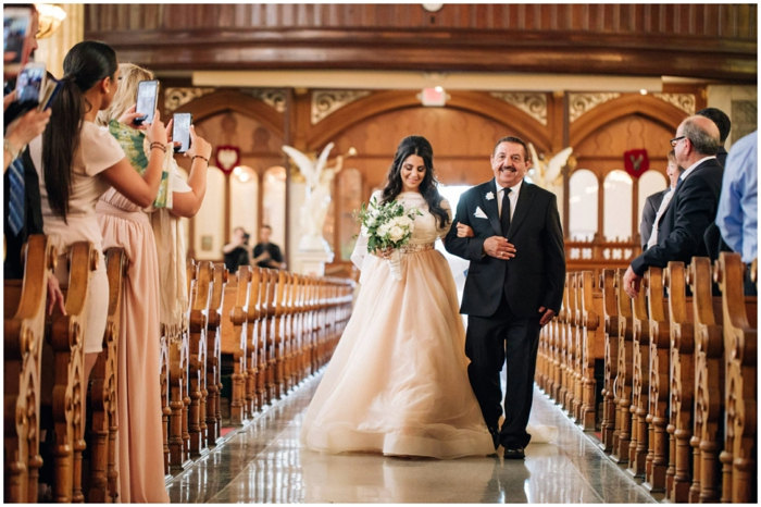 bride being walked down the aisle by her father, being photographed, wedding ceremony songs, photo from inside the chapel
