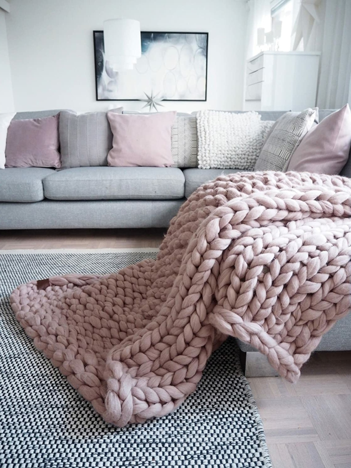 large light pink merino wool blanket, spread on a grey corner sofa, traditional anniversary gifts