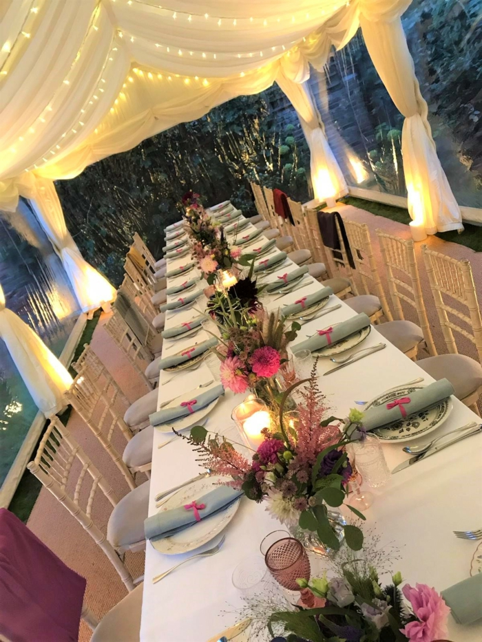 long table with plate settings, flower bouquets in the middle, tulle with fairy lights above it, 18th birthday party ideas