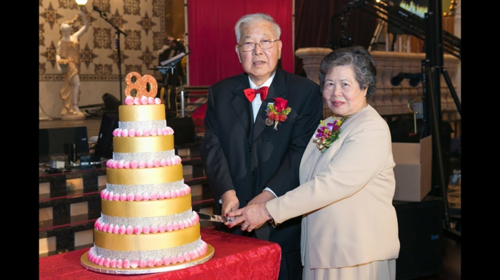man and woman standing next to a table, 80th birthday party decorations, cutting into five tier cake