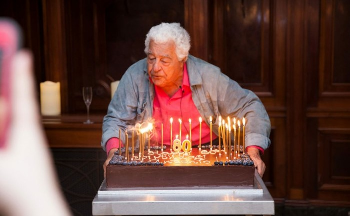 old man standing in front of a table, large chocolate cake on it, blowing out candles, 80th birthday color