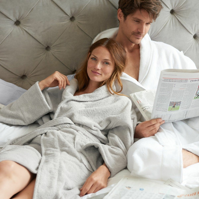 mann and woman lying in bed, wearing white and grey cozy cotton robes, anniversary gifts by year, man reading newspaper