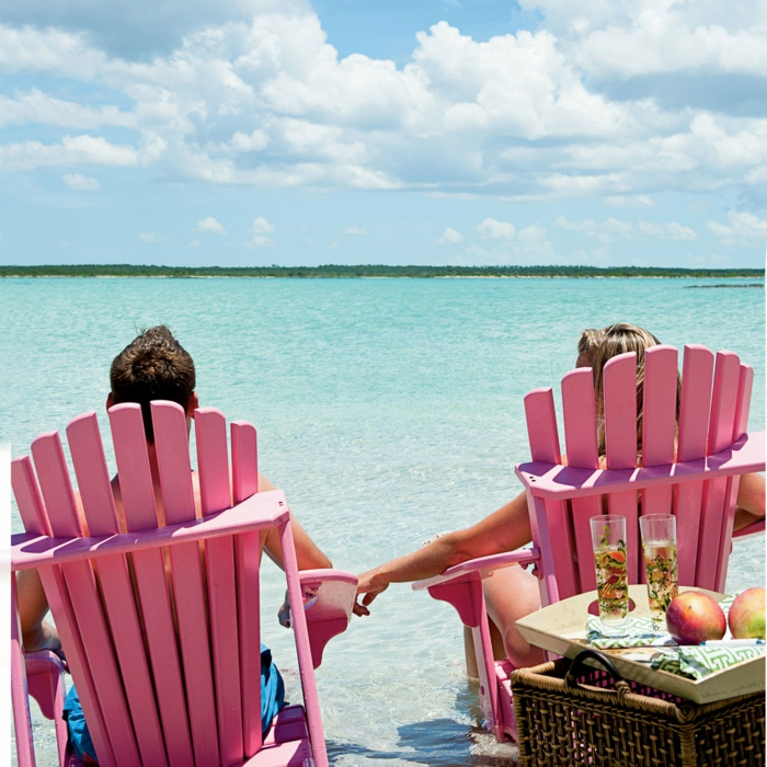 man and woman sitting on pink chairs at the beach, wedding anniversary gifts, holding hands