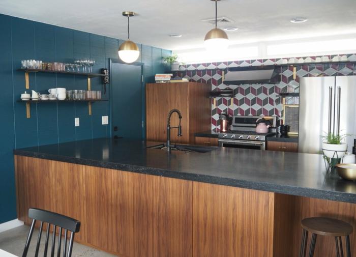 blue wall, wooden kitchen island, black granite countertops, mid century modern backsplash, tiled backsplash