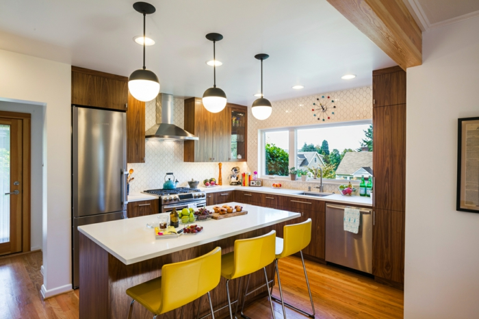 wooden cabinets with white countertops, mid century kitchen island, mustard yellow bar stools