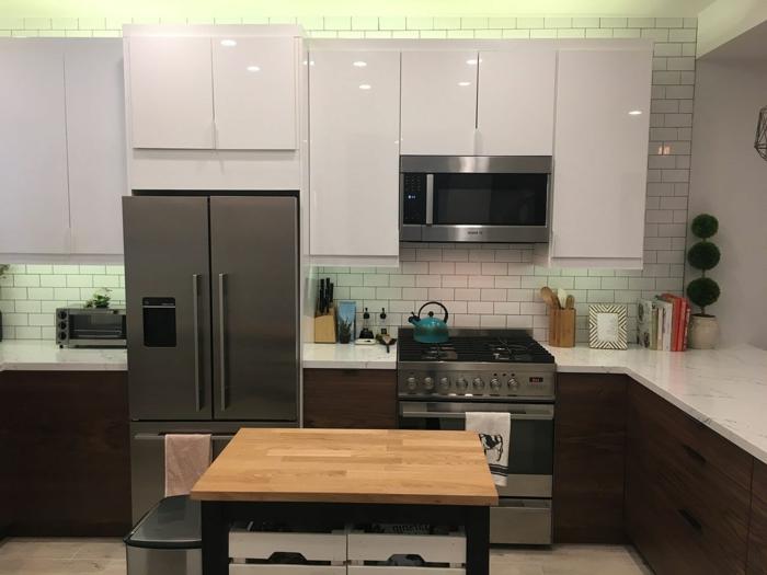 white subway tiles backsplash, mid century kitchen island, dark wooden cabinets with white countertops