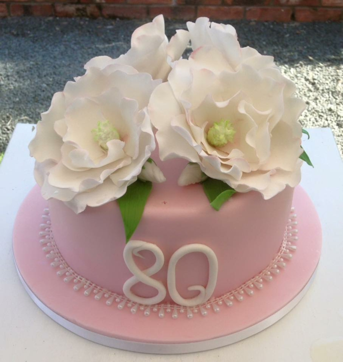 one tier cake, covered wih pink fondant, 80th birthday party decorations, decorated with white flowers