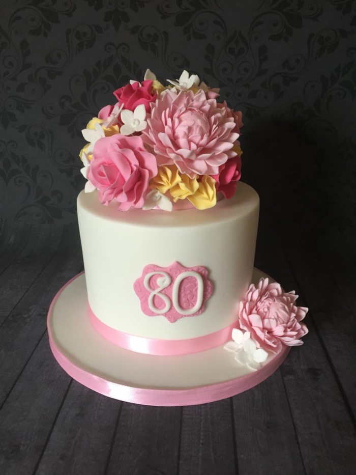 one tier cake, covered with white fondant, 80th birthday party decorations, decorated with flowers on top