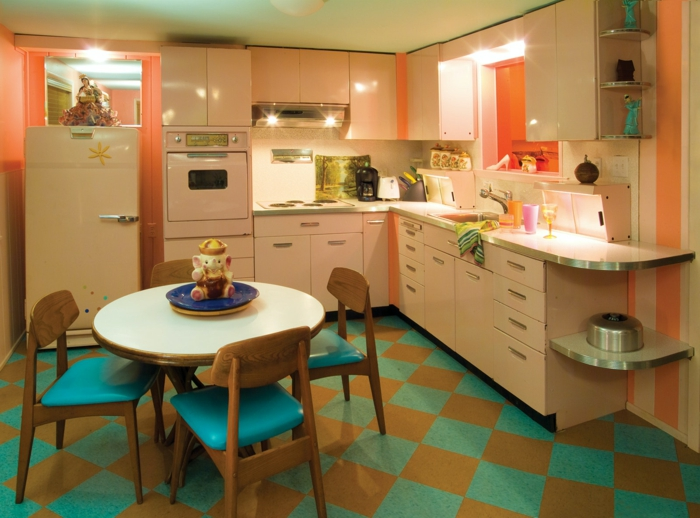 blue and orange riles on the floor, white cabinets, mid century kitchen island, blue chairs around white table