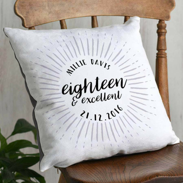 personalised throw pillow, eighteen and excellent written on it, things to do for 18th birthday, placed on wooden chair