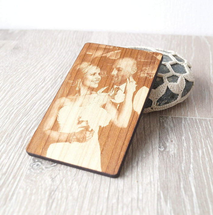 photo of the bride and groom, printed on a wooden coaster, anniversary gifts for her, placed on wooden surface