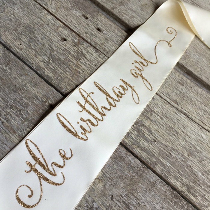 the birthday girl, white sash with gold glitter letters, 18th birthday party ideas, placed on wooden surface