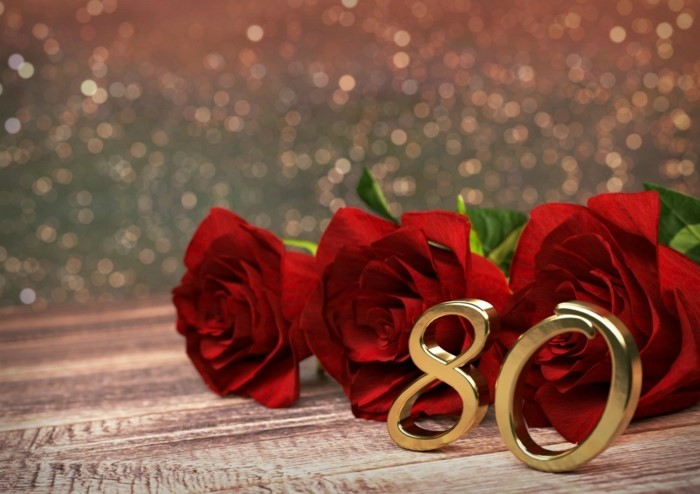 80th birthday color, three red roses, metal number eighty, placed in front of them