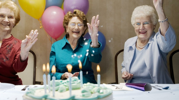 three women smiling, sitting next to a table, 80th birthday, throwing confetti in the air